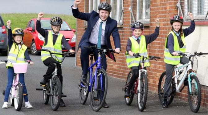 Chris Hazzard MLA, then Minister for Infrastructure, with pupils from St Colmcille's Primary School in Downpatrick on Bike to School Day in June 2016